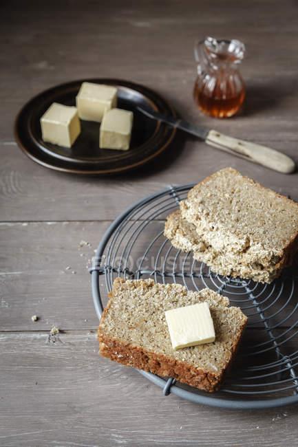 Rebanadas de pan de trigo sarraceno sin gluten caseras y pedazo de mantequilla en la rejilla de refrigeración - foto de stock