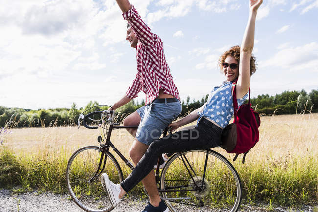 Happy young couple riding bicycle on road in countryside — Stock Photo