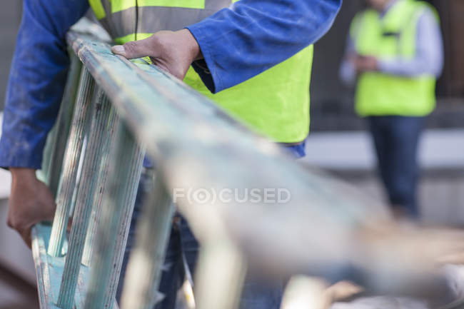 Cropped image of construction worker carrying a ladder — Stock Photo