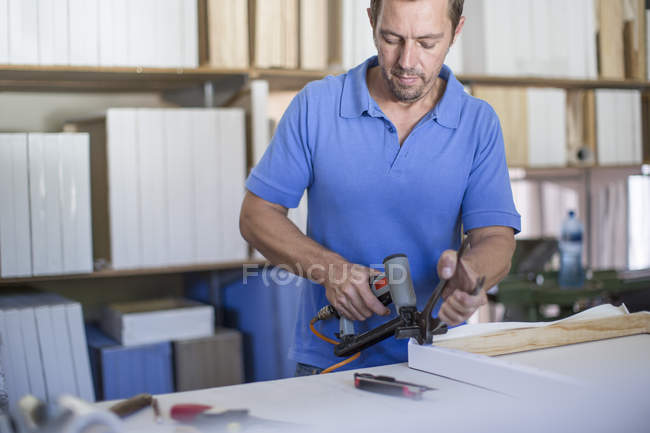 Man working on frame in canvas workshop — Stock Photo