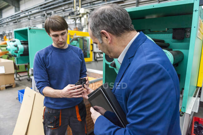 Manager and worker in plastics factory discussing production quality — Stock Photo