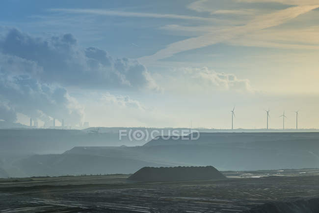 Germany, North Rhine-Westphalia, Garzweiler surface mine, brown coal power station and wind turbines in background — Stock Photo