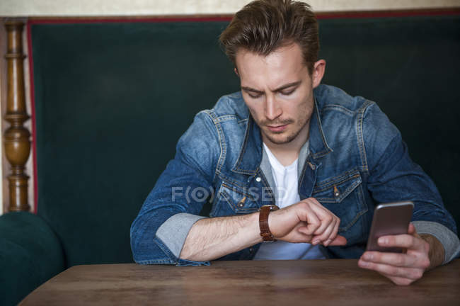Portrait of angry young man sitting in a coffee shop checking the time — Stock Photo
