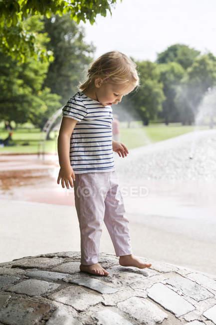 Little girl standing barefoot on cobblestones — Stock Photo