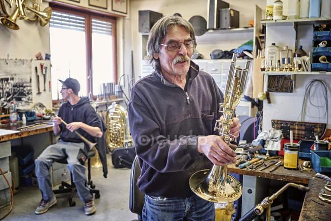 Instrument maker examining trumpet in workshop — Stock Photo