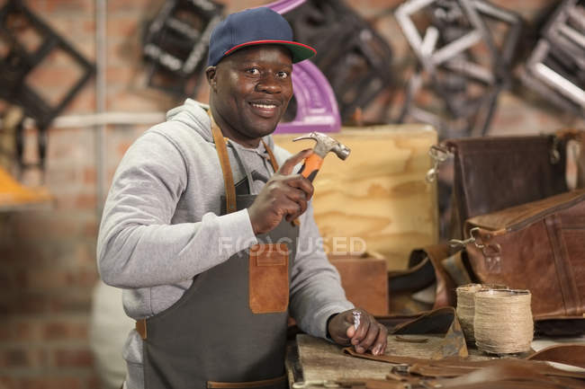 Portrait of smiling man working with hammer in leather workshop — Stock Photo