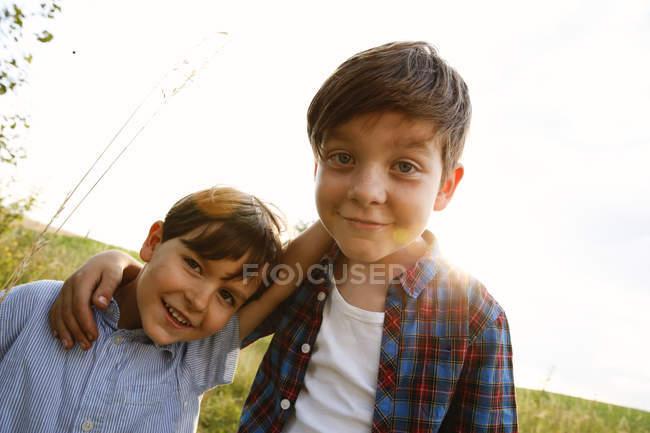 Портрет двух улыбающихся мальчиков на подсветке — стоковое фото