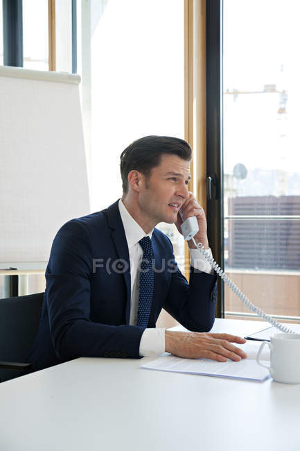 Businessman at office desk on the phone — Stock Photo