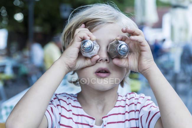 Menino cobrindo os olhos com potes de sal e pimenta — Fotografia de Stock