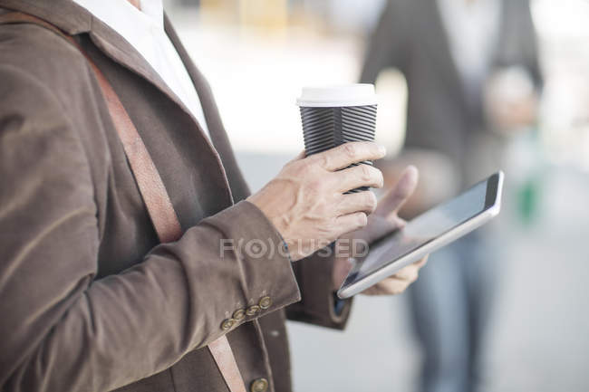 Man with digital tablet and coffee to go outdoors — Stock Photo