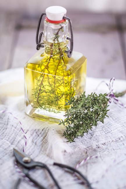 Close-up de galhos de tomilho no azeite de oliva, óleo de tomilho — Fotografia de Stock