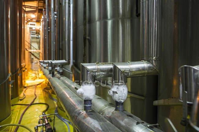 Pipework of industrial steel tanks infoors — Stock Photo