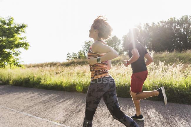 Молодая пара бегает по дороге в сельской местности — стоковое фото