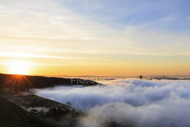 États-Unis, Californie, San Francisco, horizon et Golden Gate Bridge dans le brouillard au lever du soleil — Photo de stock