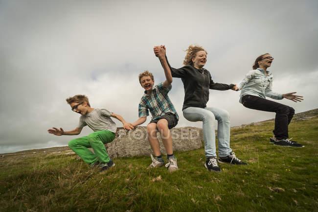 Vereinigtes Königreich, England, Kornwand, Kinder springen vom Stein — Stockfoto