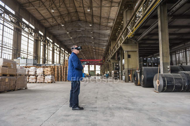 Manager standing in factory hall looking through VR glasses — Stock Photo