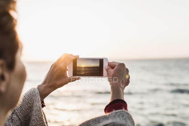 França, península de Crozon, mulher tirando uma foto do pôr do sol com smartphone — Fotografia de Stock