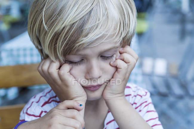 Porträt eines kleinen blonden Jungen mit dem Kopf in den Händen — Stockfoto