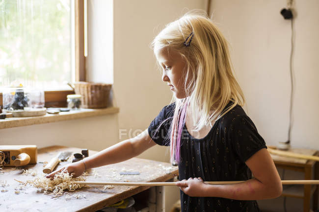 Girl in workshop working on stone-age spear-thrower — Stock Photo