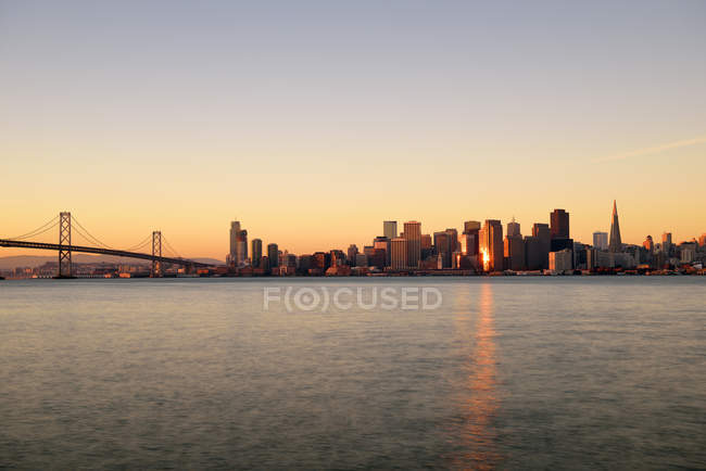 USA, Kalifornien, San Francisco, Oakland Bay Bridge und Skyline des Finanzdistrikts im Morgenlicht — Stockfoto