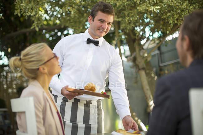 Garçom servindo comida à mesa para duas pessoas — Fotografia de Stock
