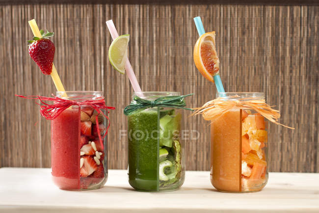 Red, green and orange vegetable and fruit smoothies in glasses with straws — Stock Photo