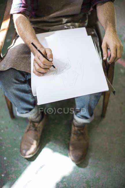 Обрезанное изображение человека, рисующего в альбоме — стоковое фото