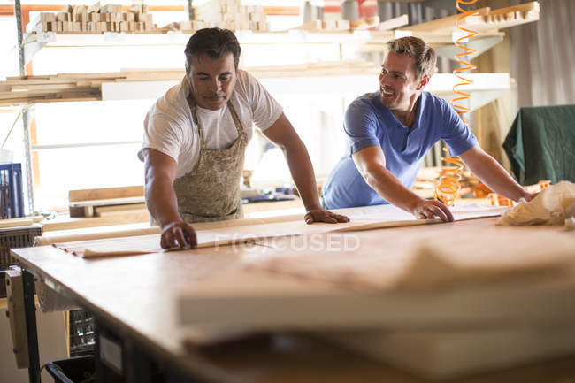 Two men working together in canvas workshop — Stock Photo