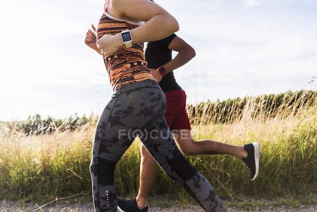 Активная пара, работающая на пути к полю — стоковое фото