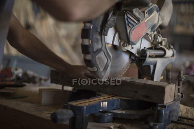 Плотник, работающий с циркулярной пилой в цехе — стоковое фото