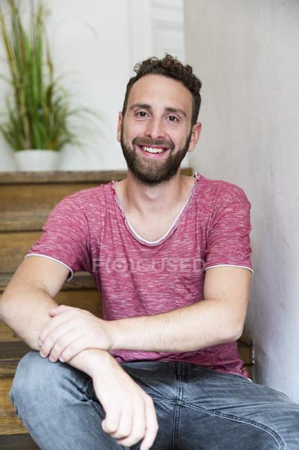 Улыбающийся молодой человек сидит на лестнице — стоковое фото
