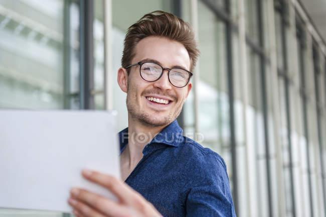 Ritratto di giovane uomo d'affari sorridente con tablet digitale — Foto stock