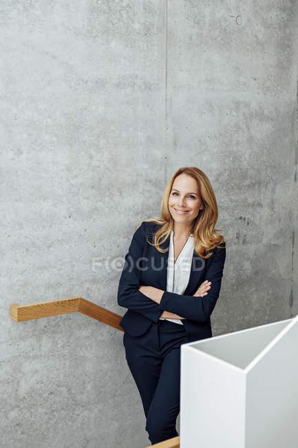 Портрет улыбающейся деловой женщины на лестнице — стоковое фото