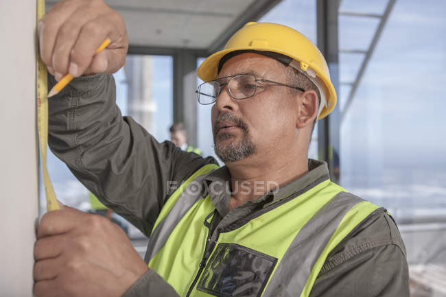 Construction worker measuring on construction site — Stock Photo