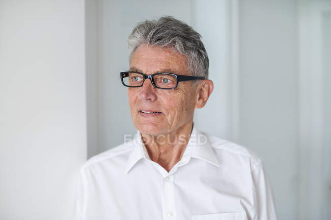 Старший чоловік носить окуляри і білу сорочку — стокове фото