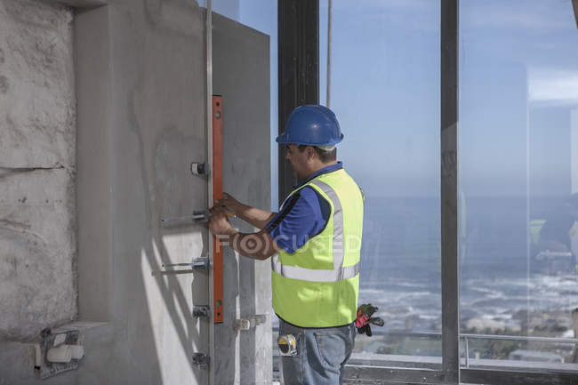Construction worker using spirit level on construction site — Stock Photo