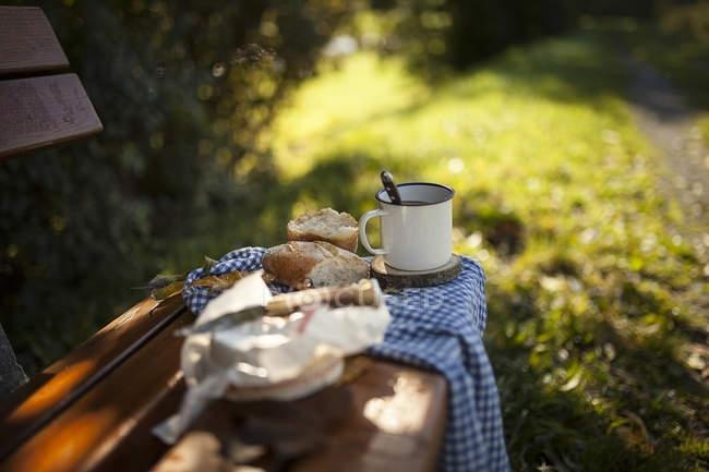 Caffè, pane, formaggio e foglie autunnali su panca di legno — Foto stock