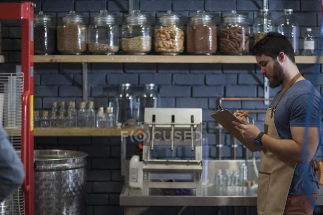 Человек, делающий заметки на планшете в винокурне — стоковое фото