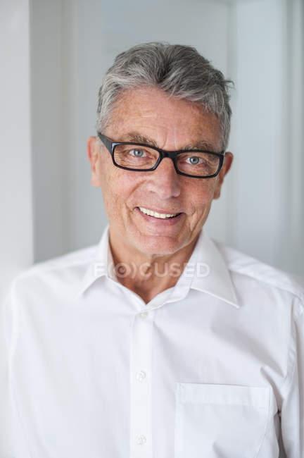 Портрет усміхнений старший чоловік носить окуляри і білу сорочку — стокове фото