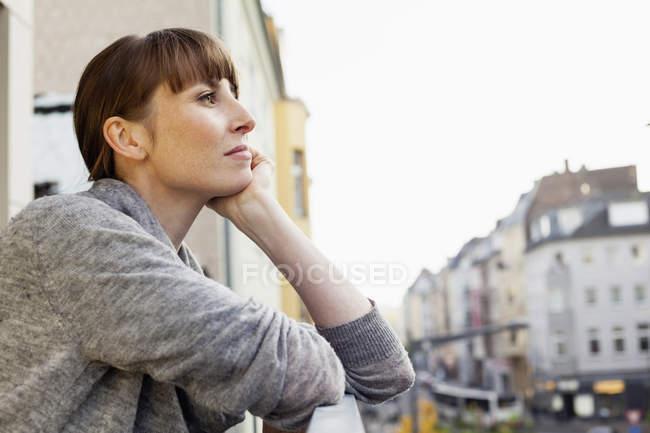 Ernsthaft nachdenkliche Frau steht auf Balkon — Stockfoto