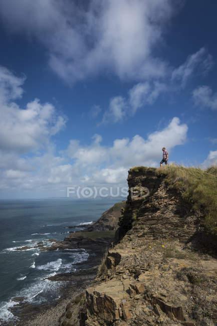 Alpinista de pé no alto de um precipício de dia — Fotografia de Stock
