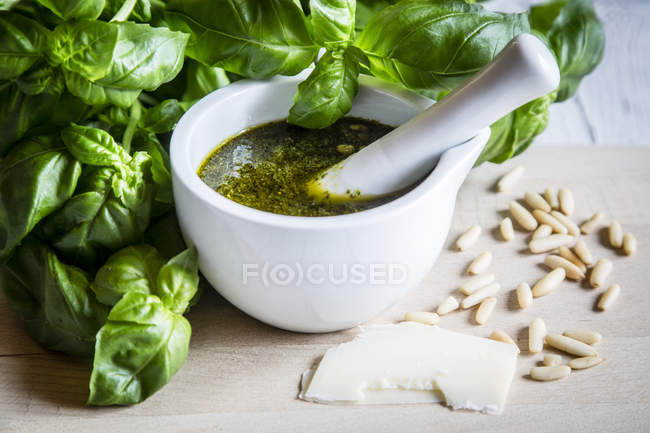 Mortar of homemade pesto Genovese and green basil leaves with pine nuts — Stock Photo