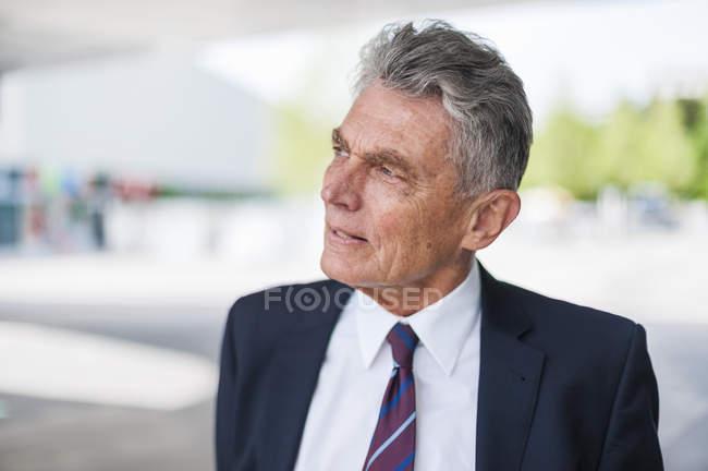 Retrato de hombre de negocios senior mirando hacia los lados - foto de stock