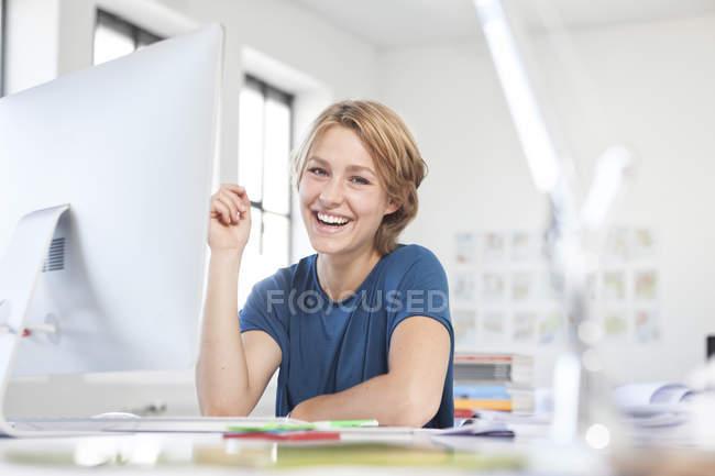 Porträt einer glücklichen jungen Frau an ihrem Schreibtisch in einem kreativen Büro — Stockfoto