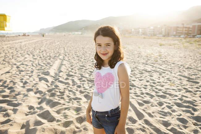 Retrato de una niña sonriente en la playa - foto de stock