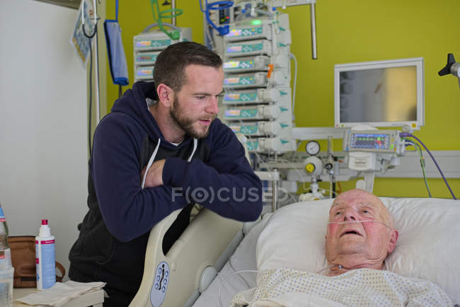 Grandson visiting grandfather in intensive care after heart attack — Stock Photo