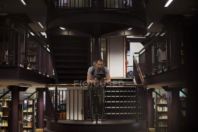 Студент с помощью цифрового планшета в библиотеке — стоковое фото