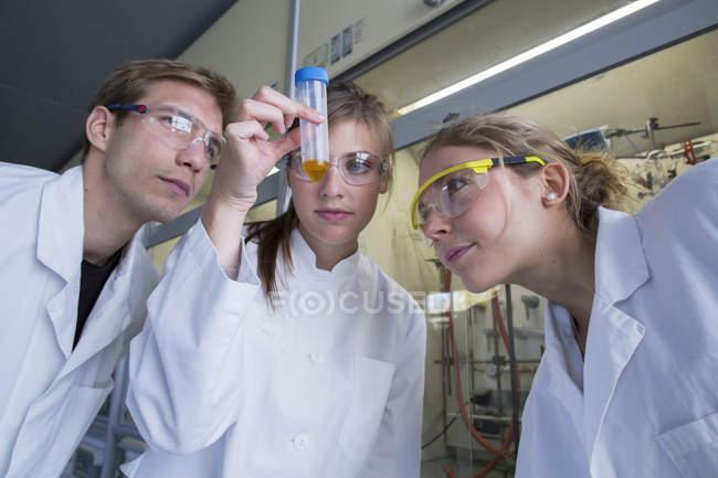 Trois chimistes travaillant dans un laboratoire de chimie en regardant éprouvette — Photo de stock