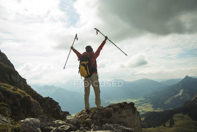 Woman cheering on mountain top — Stock Photo