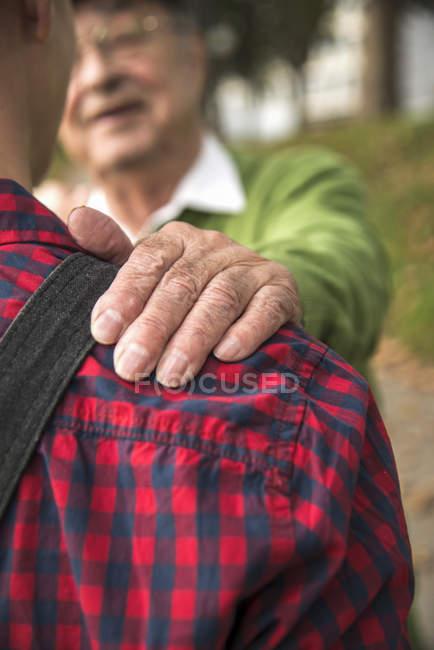 Close-up of Senior man putting hand on grandson shoulder — Stock Photo